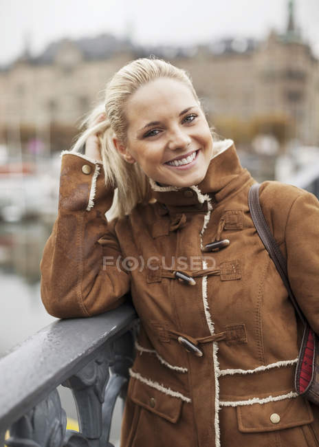 Portrait of happy woman leaning on railing outdoors — Stock Photo