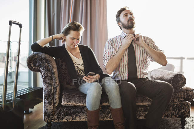 Business couple relaxing on chaise longue in hotel room — Stock Photo