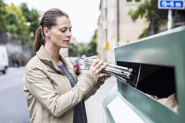 Femme adulte moyenne mettant des journaux dans la poubelle de recyclage — Photo de stock