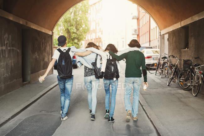 Vue arrière d'adolescents avec les bras autour de la marche dans des vélos tunnel — Photo de stock