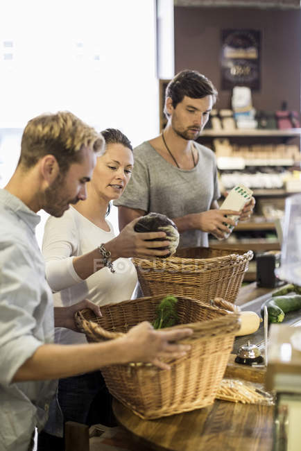 Friends with basket of groceries at supermarket checkout — Stock Photo