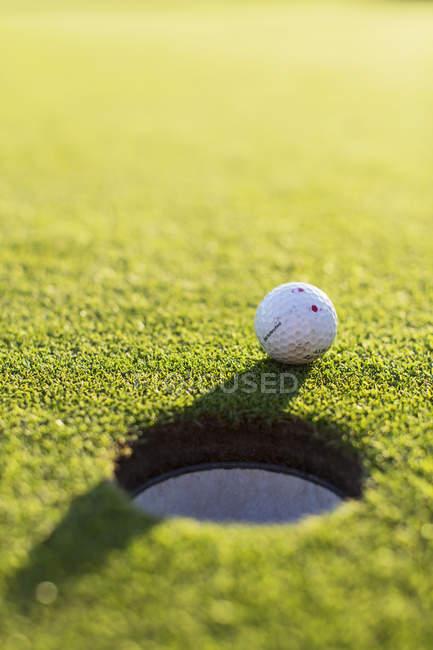 М'яч для гольфу за отвір на поле зелені гольф — стокове фото