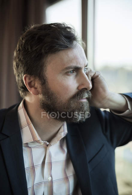 Thoughtful businessman leaning on window in hotel — Stock Photo