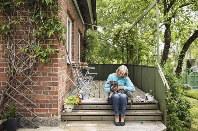 Happy woman sitting with dog on steps outside house — Stock Photo