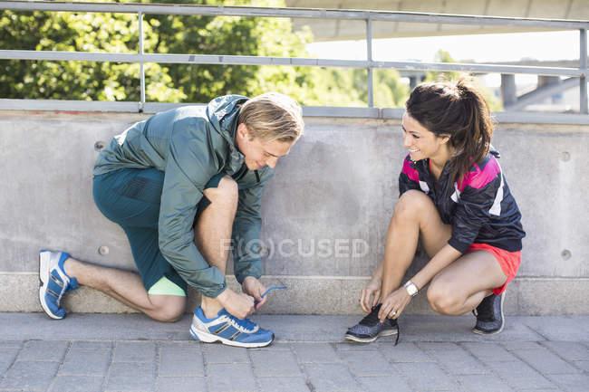 Souriant couple fit attacher lacets avant de faire du jogging sur le pont — Photo de stock