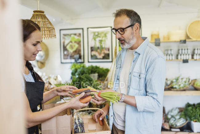 Mature man buying carrots from female clerk at food store — Stock Photo