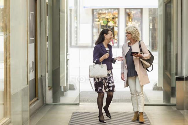 Senior amiche di sesso femminile parlando mentre si cammina nel centro commerciale — Foto stock