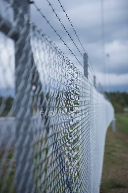 Selective focus of fence with barbed wire, outdoors — Stock Photo