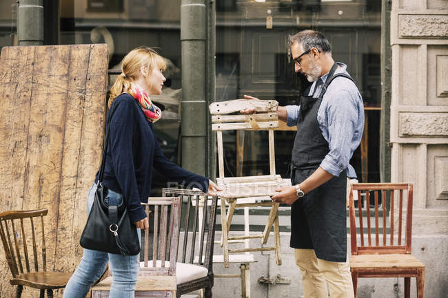 Costumer and owner discussing over chair outside shop — Stock Photo