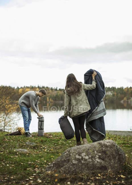 Giovani coppie con coperta e sacco a pelo a lakeshore — Foto stock