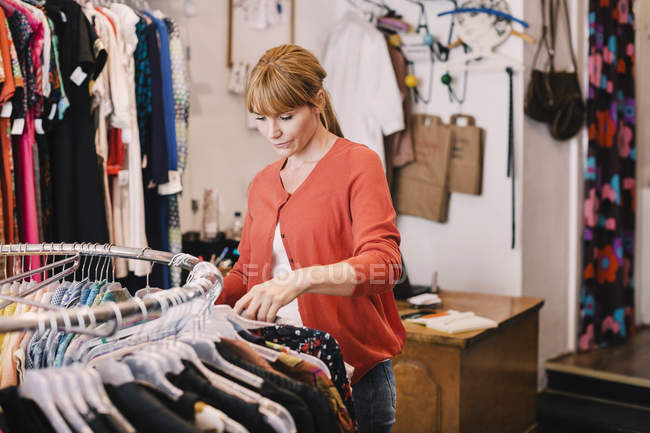 Owner arranging clothes on rack while standing at thrift store — Stock Photo