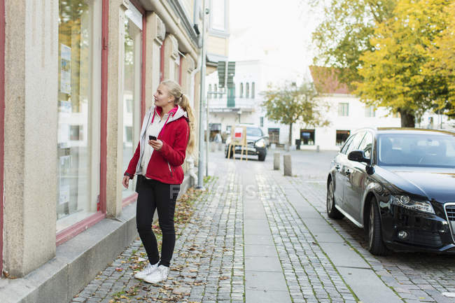 Full length of teenage girl window shopping — стокове фото