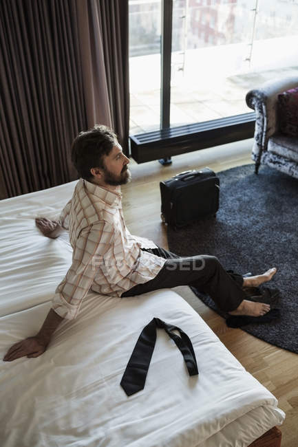 High angle view of  businessman relaxing on bed in hotel room — Stock Photo