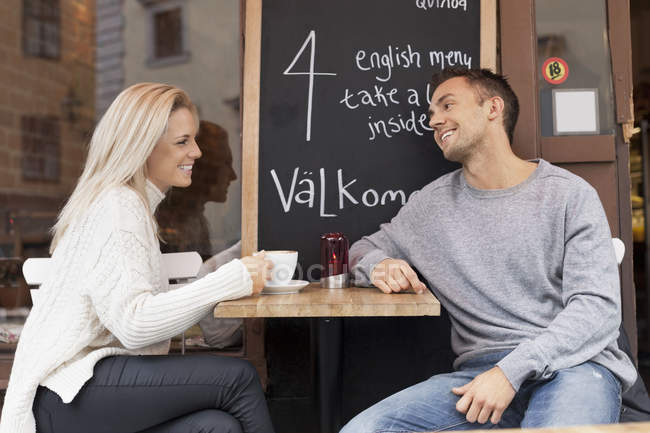 Young couple spending leisure time at outdoor cafe — стокове фото