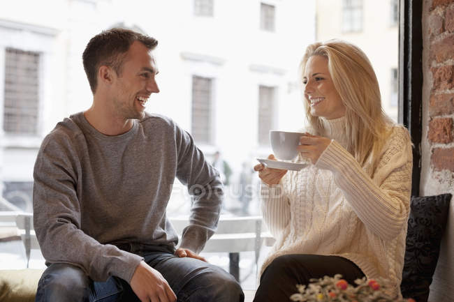 Happy young couple spending leisure time at cafe — стокове фото