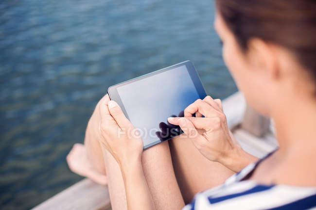 Vista de ángulo alto de la mujer madura usando tableta digital en el muelle - foto de stock