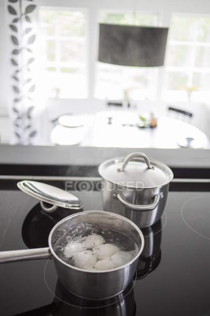Яйця киплячу сковороду на печі в кухні — стокове фото
