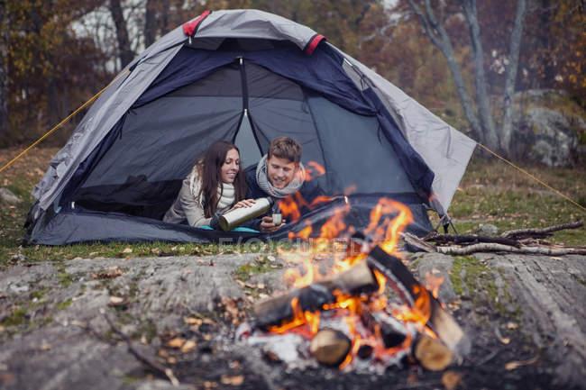 Mulher derramando café para o homem enquanto estava deitado na tenda na floresta — Fotografia de Stock