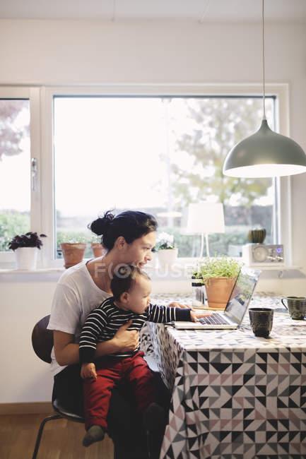 Mãe carregando bebê menina olhando no laptop enquanto sentado na cozinha — Fotografia de Stock