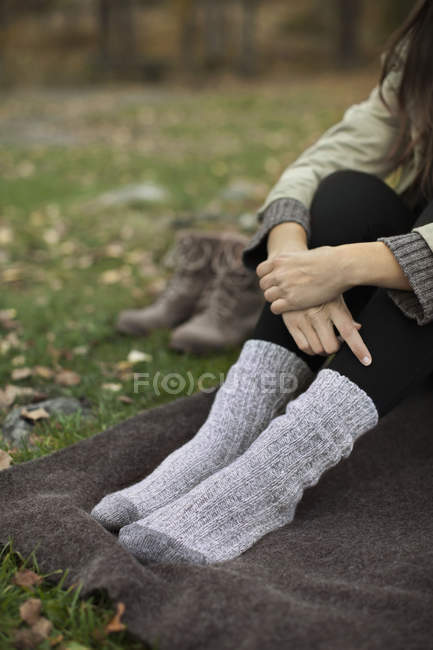 Low section of woman wearing socks sitting on blanket while camping — Stock Photo