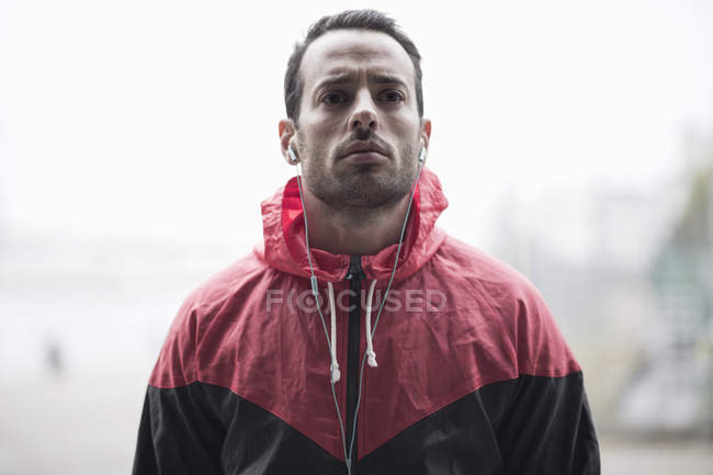 Sporty man in jacket listening to music through earphones — Stock Photo