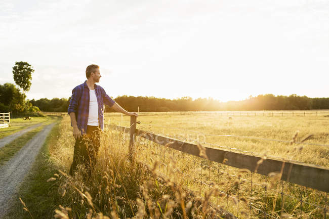 Farmer standing by fence on grassy field during sunny day — Stock Photo