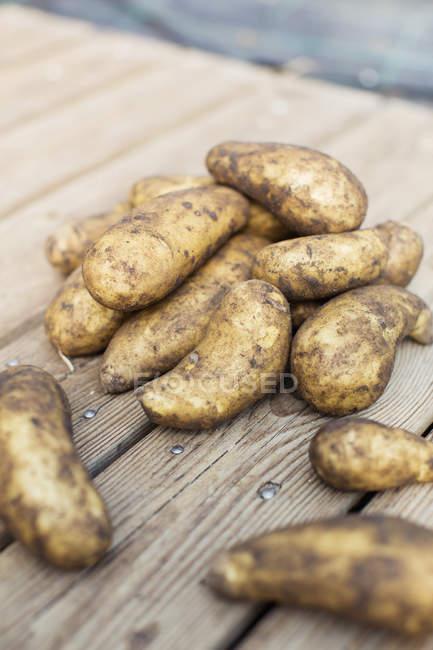 Pommes de terre Sales sur la surface en bois à l'extérieur — Photo de stock