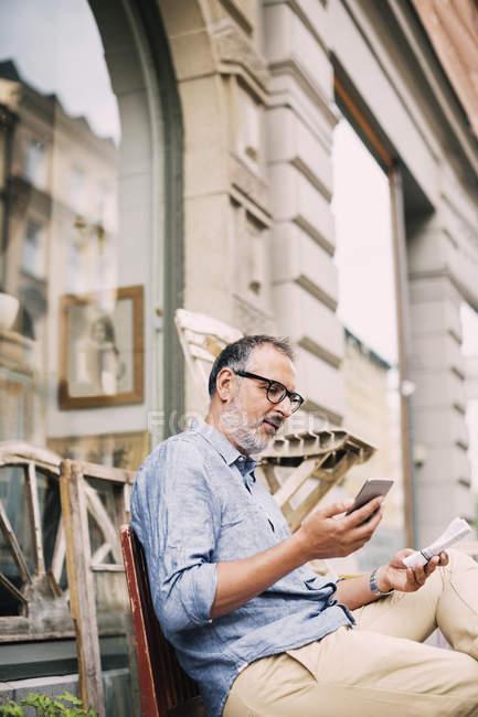 Uomo che usa il telefono cellulare mentre è seduto fuori dal negozio — Foto stock