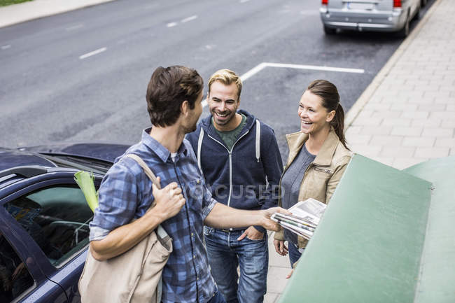 Heureux amis avec l'homme de mettre le journal dans la poubelle — Photo de stock