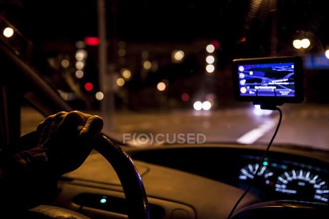 Cropped image of man driving car at night — Stock Photo