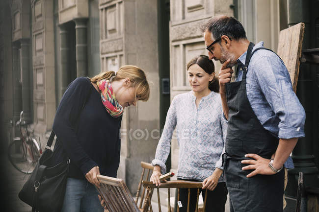 Female costumer choosing chair while retailers standing outside antique shop — Stockfoto