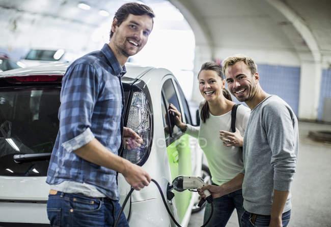 Porträt glücklicher Freunde mit Mann beim Laden von Elektroauto an Tankstelle — Stockfoto