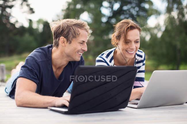 Feliz pareja madura usando computadoras portátiles mientras está acostado en el muelle - foto de stock