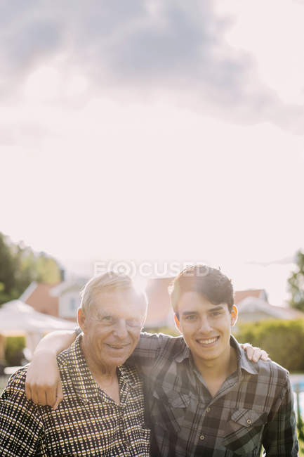 Portrait of happy grandfather and grandson with arms around against sky — Stock Photo