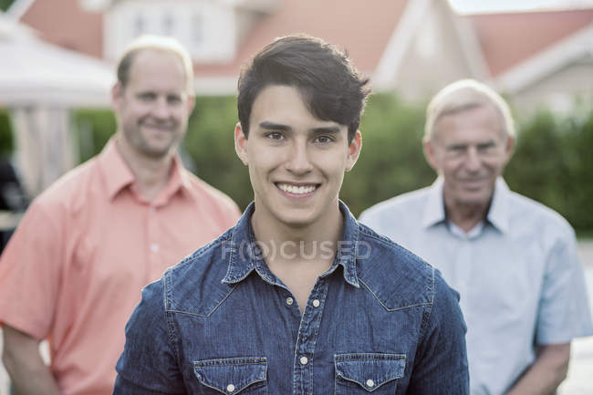 Portrait of confident young man with grandfather and father standing in yard — Stock Photo