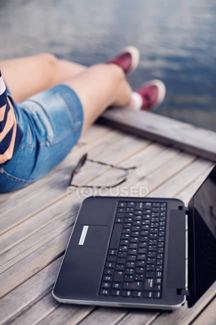 Low section of woman sitting by laptop on pier — Stock Photo