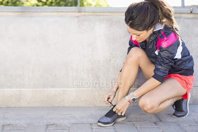 Toute la longueur de la femme fit attacher le lacet avant de faire du jogging sur le pont — Photo de stock
