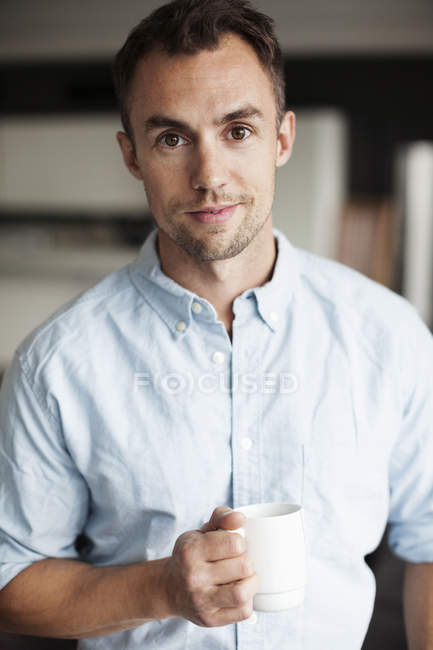 Portrait of confident businessman holding coffee mug in office — Stock Photo