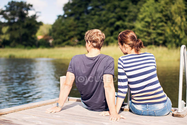 Rear view of mature couple relaxing on pier at lake — Stock Photo