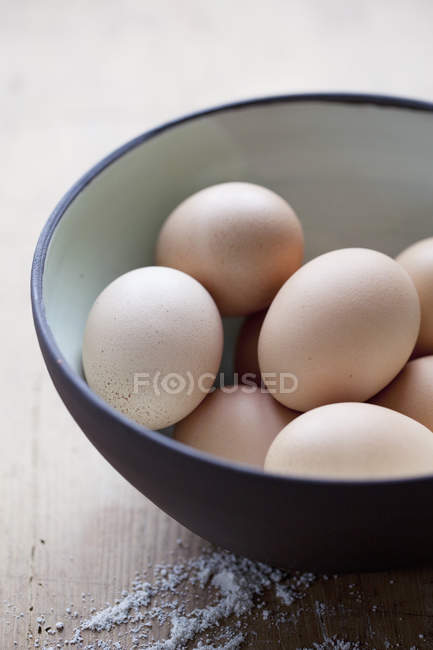 Яйца в миску на столе — стоковое фото