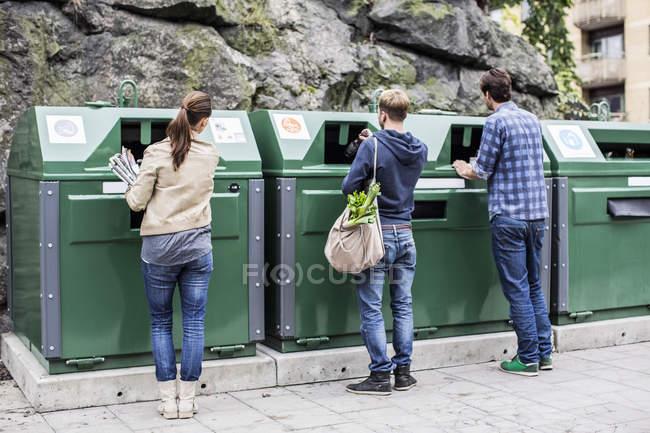 Vue arrière d'amis mettant des matériaux recyclables dans des bacs de recyclage — Photo de stock