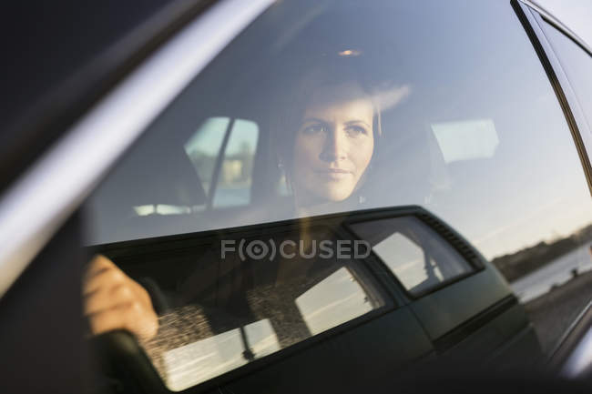 Femme d'affaires regardant par la fenêtre tout en conduisant la voiture — Photo de stock