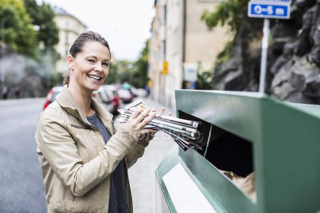 Portrait de femme souriante mettant des journaux dans la poubelle de recyclage — Photo de stock