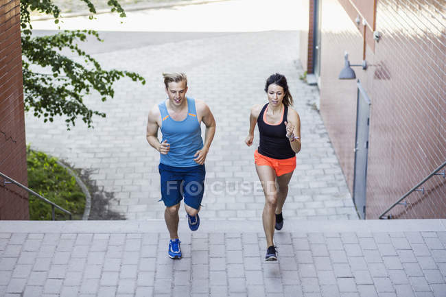 Full length of fit couple running on steps outdoors — Stock Photo