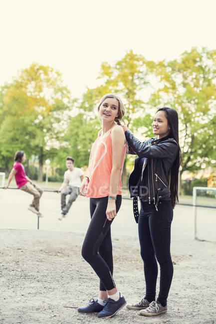 Schüler flechtet Freundin auf Schulhof die Haare — Stockfoto