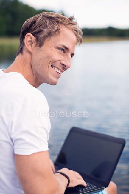 Sorrindo homem maduro usando laptop enquanto olha para o lago — Fotografia de Stock