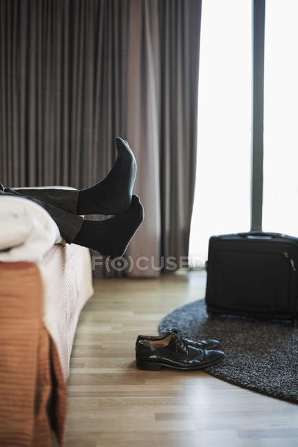Low section of businessman relaxing on bed in hotel room — Stock Photo