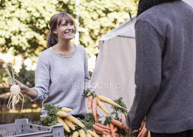 Young female vendor selling vegetables at market stall — Stock Photo