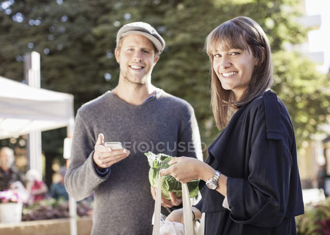 Portrait of smiling couple with mobile phone and groceries in market — Stock Photo