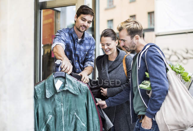 Friends shopping for jackets at clothing store — Stock Photo